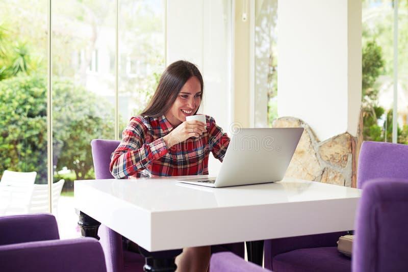 La jeune brune apprécie le café tout en travaillant avec l'ordinateur portable images stock