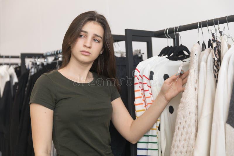 La jeune brune choisit son survêtement dans le magasin photographie stock libre de droits