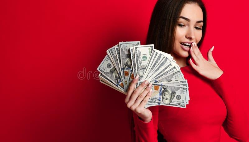 La jeune brune effrontée dans une robe rouge est étonnée à une pile des billets d'un dollar d'argent dans sa main photographie stock