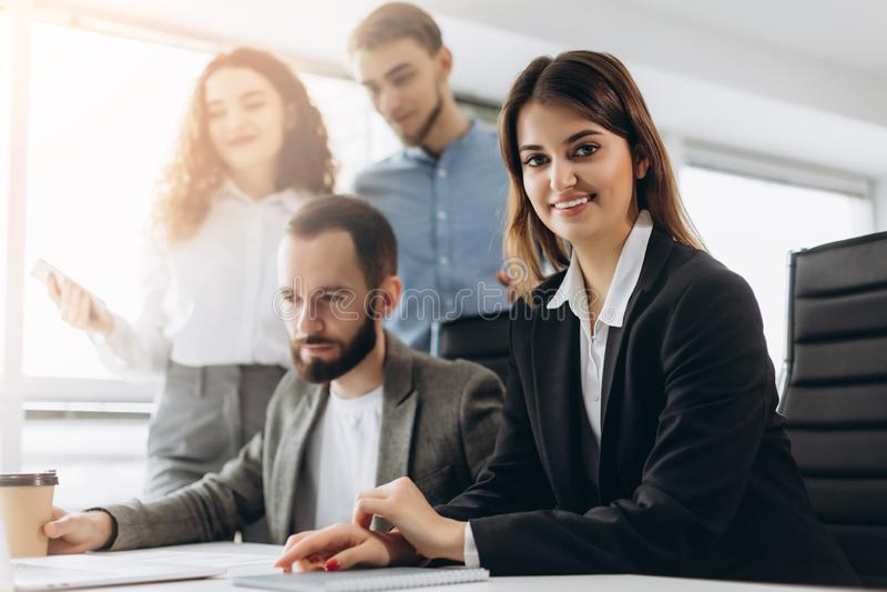 La jeune dame attirante d'affaires regarde l'appareil-photo et sourit tandis que ses collègues travaillent à l'arrière-plan photos stock