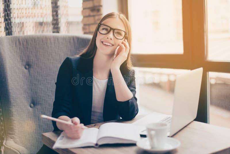 La jeune dame avec du charme de sourire d'affaires parle au téléphone dedans image libre de droits