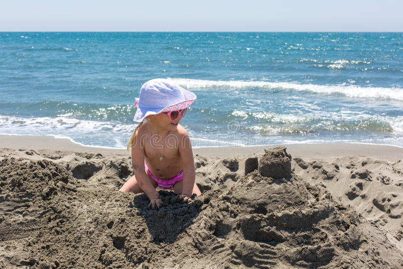 La jeune dame construit un château de sable photo libre de droits