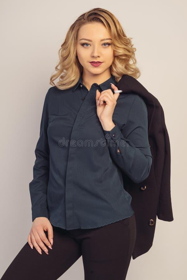 La jeune dame d'affaires se tient tenante une veste sur son épaule photos stock