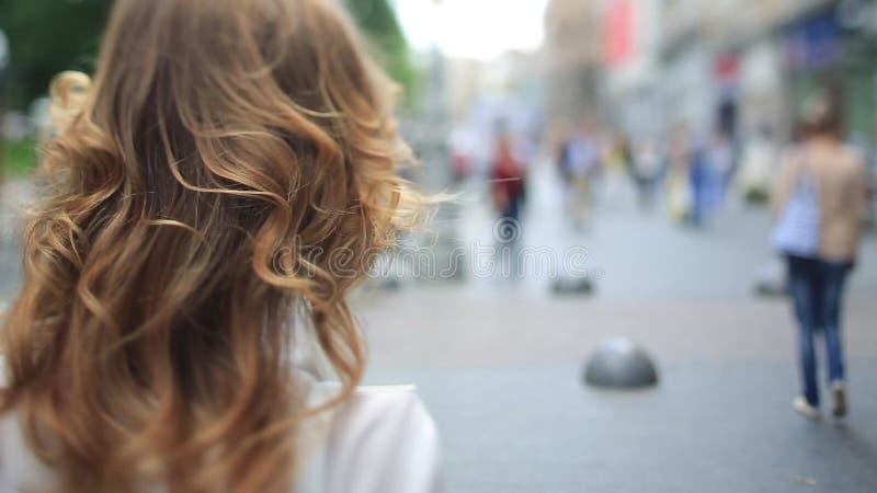 La jeune dame de mode sexy dans les jeans et des chaussures rouges élégantes marche sur la rue urbaine par la foule banque de vidéos