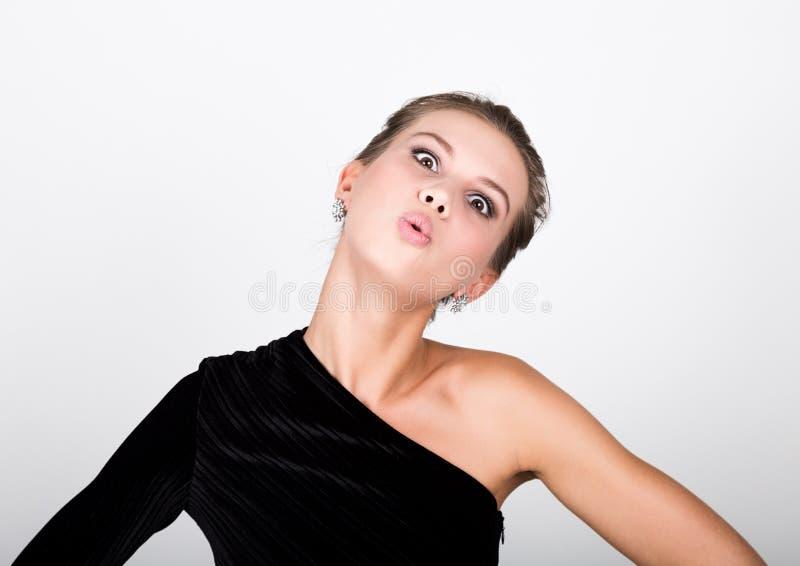 La jeune dame de photo en gros plan de mode dans la robe noire élégante, femme espiègle sourit et envoie un baiser d'air photos stock