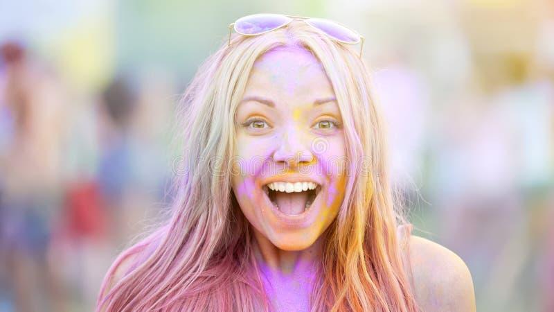 La jeune dame enthousiaste couverte dans Holi colore l'appareil-photo de sourire, ayant l'amusement au festival photographie stock