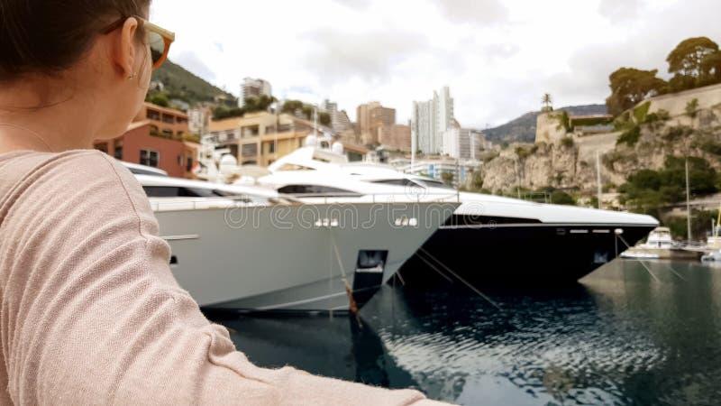 La jeune dame s'asseyant sur le banc près de la mer, regardant des yachts garés au pilier, détendent photos stock