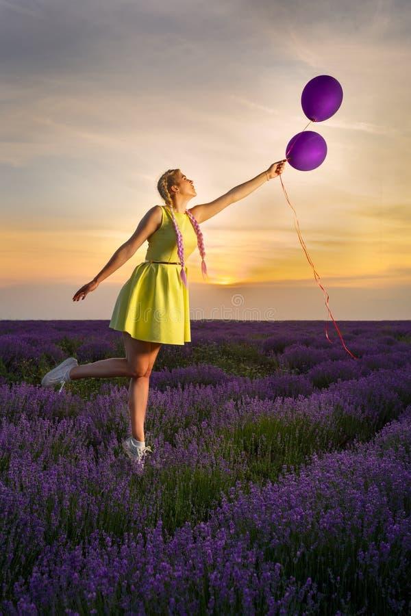 La jeune et belle fille dans le vol jaune de robe au ciel et à l'exploitation monte en ballon dans sa main À l'arrière-plan, un g photo libre de droits