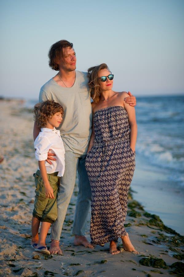 La jeune famille admire un coucher du soleil sur la côte images libres de droits
