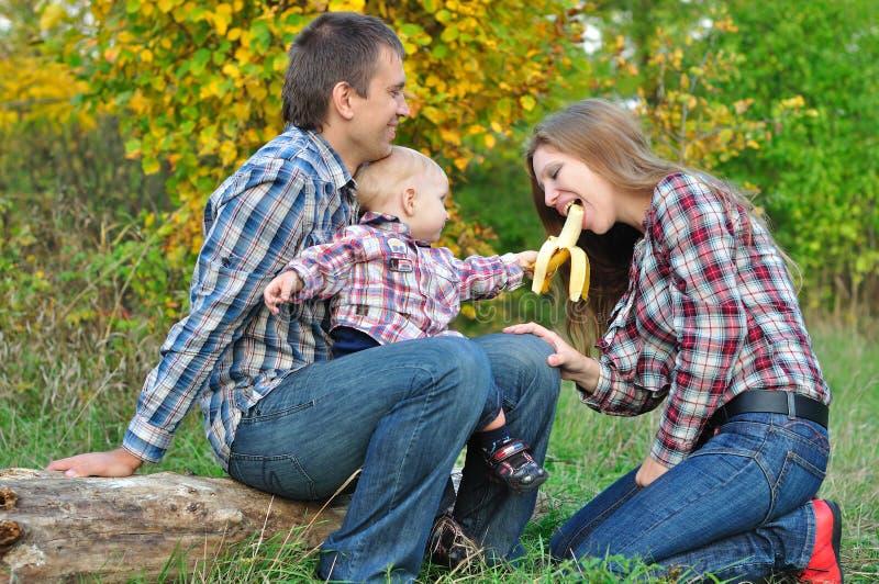La jeune famille dans le garçon de forêt d'automne traite la banane de maman photographie stock libre de droits