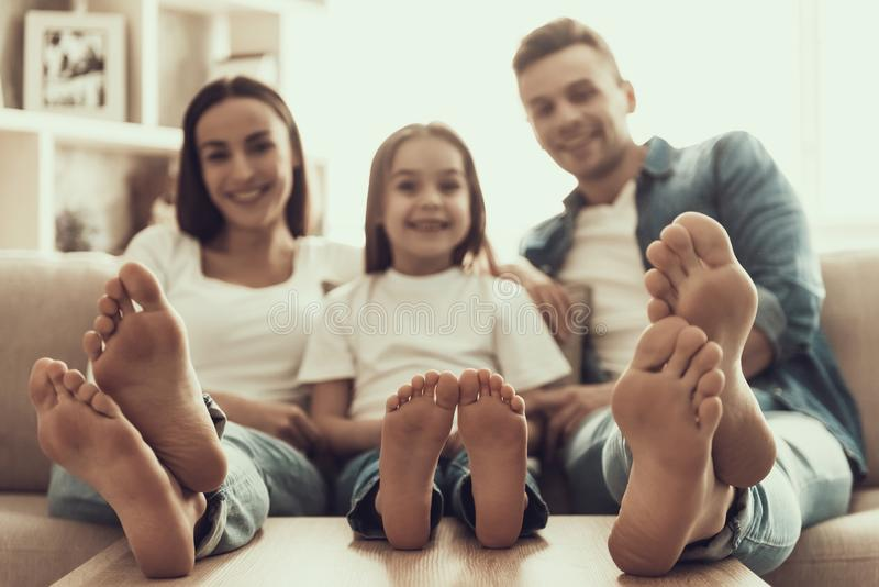 La jeune famille heureuse met les pieds nus sur le Tableau à la maison image stock