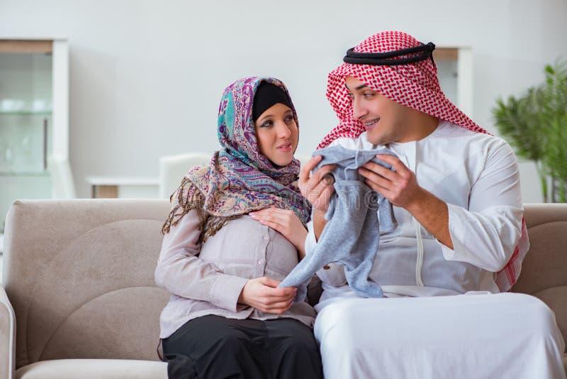 La jeune famille musulmane arabe avec l'épouse enceinte attendant le bébé photo stock