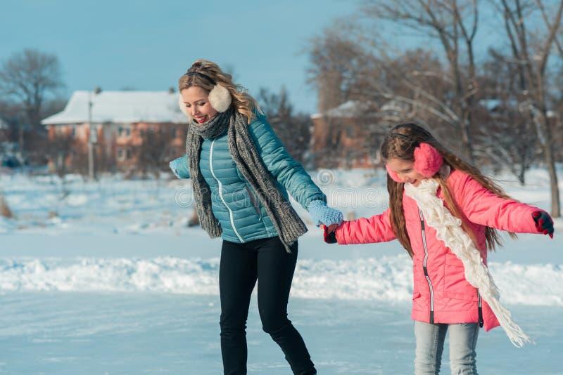 La jeune famille ont l'amusement sur le secteur de glace dans un parc neigeux photo libre de droits