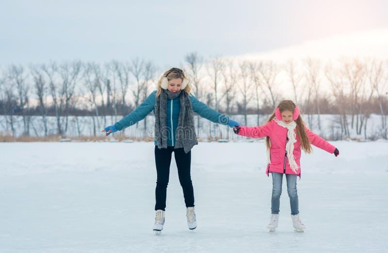 La jeune famille ont l'amusement sur le secteur de glace dans un parc neigeux images stock