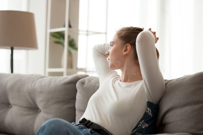 La jeune femelle détendent sur le divan regardant dans la pensée de distance photographie stock libre de droits