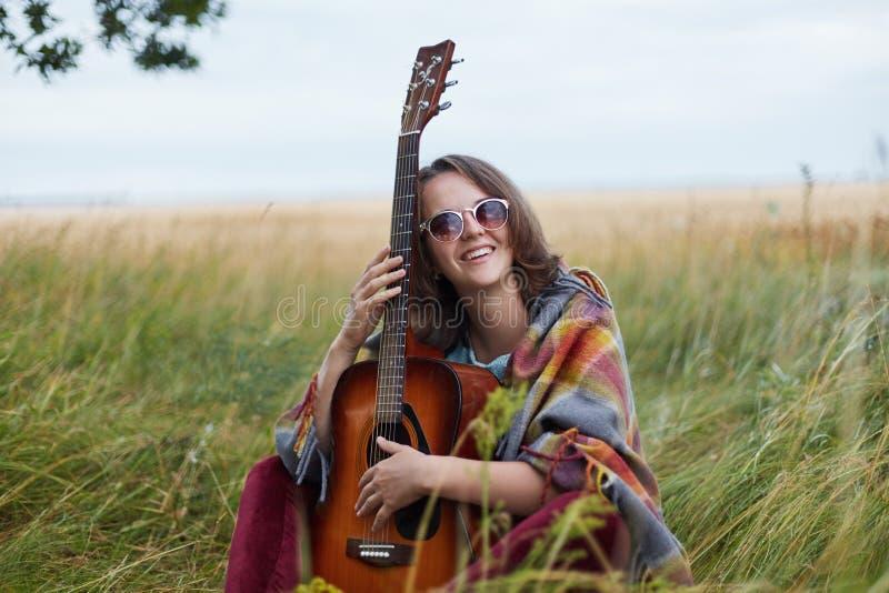La jeune femelle douée a habillé tenir en passant la guitare souriant largement à l'appareil-photo ayant la bonne humeur pour avo photo stock