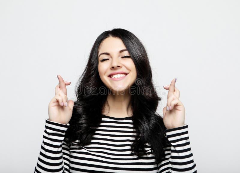 La jeune femelle joyeuse, doigts d'augmenter a crois?, fait le souhait souhaitable image libre de droits