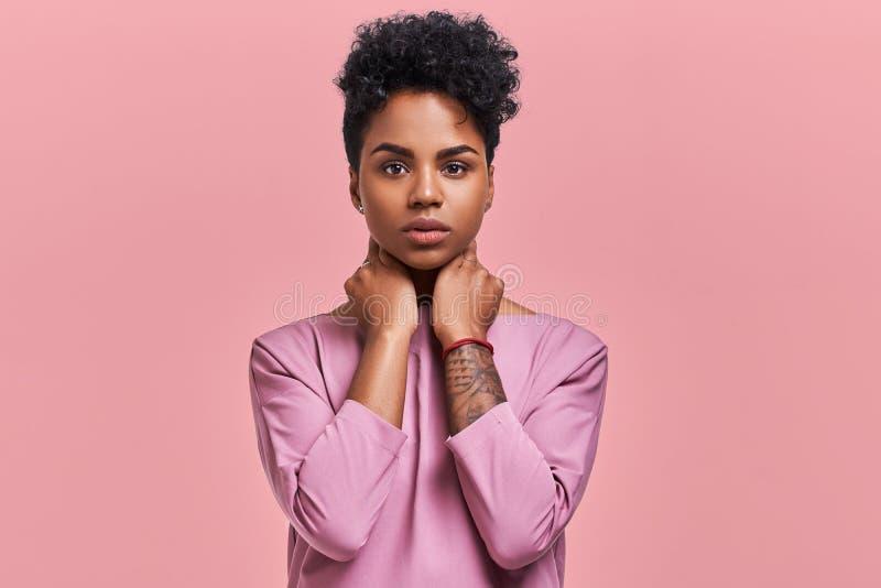 La jeune femelle pelée foncée magnifique avec la coiffure d'Afro et le regard sûr, pose pour la magazine à la mode, regarde photographie stock
