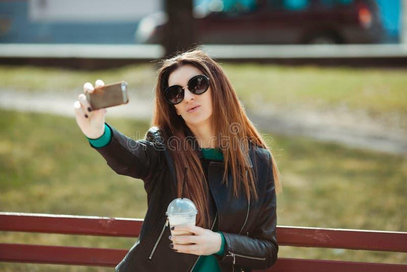 La jeune femme à l'aide d'un téléphone fait le selfie photographie stock