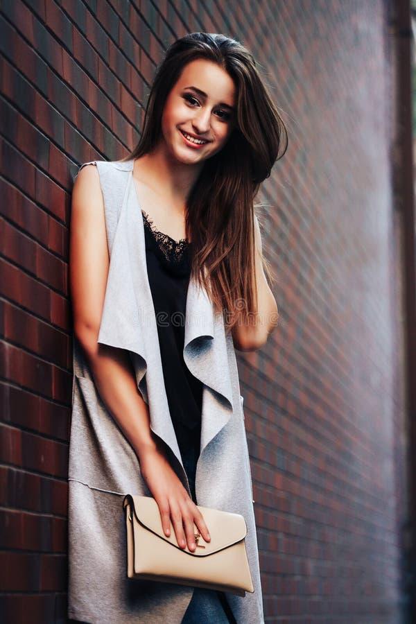 La jeune femme à la mode élégante de brune dans un cardigan beige se tient près d'un mur de briques avec un embrayage ou une bour images libres de droits