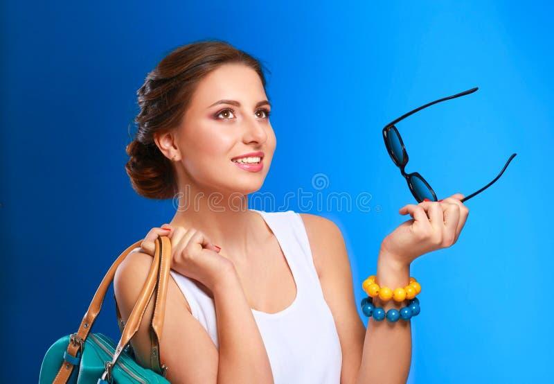 La jeune femme à la mode dans des lunettes de soleil tenant le sac image stock