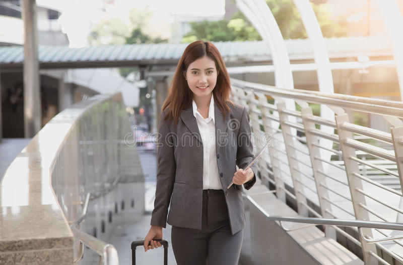 La jeune femme élégante d'affaires de l'Asie avec le bagage de main et marquent sur tablette a photographie stock libre de droits