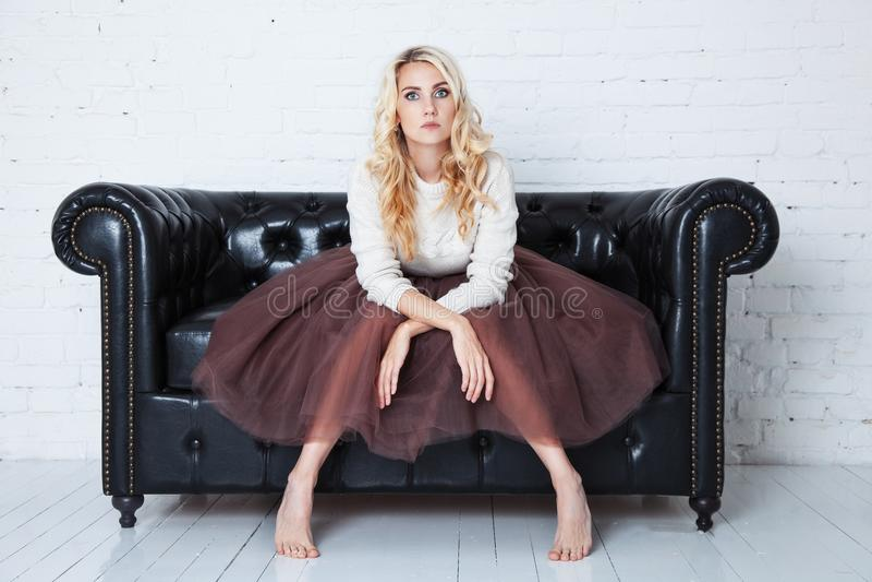 La jeune femme élégante dans la jupe luxuriante s'assied sur le divan photo libre de droits
