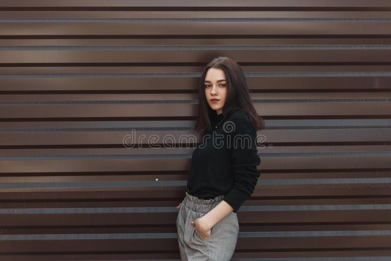 La jeune femme élégante de brune avec le maquillage naturel dans un chandail noir de cru dans le pantalon à carreaux se tient une images libres de droits