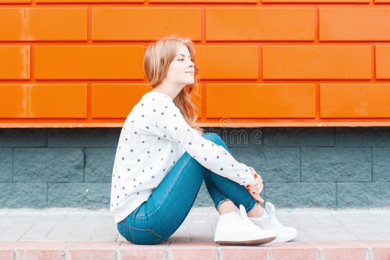 La jeune femme élégante européenne moderne dans des jeans de cru dans des espadrilles dans un chandail s'assied sur le trottoir p photo libre de droits