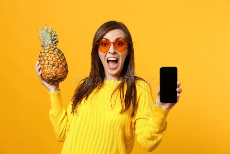 La jeune femme étonnée dans des lunettes de soleil tiennent le fruit d'ananas, téléphone portable avec l'écran vide vide d'isolem images libres de droits
