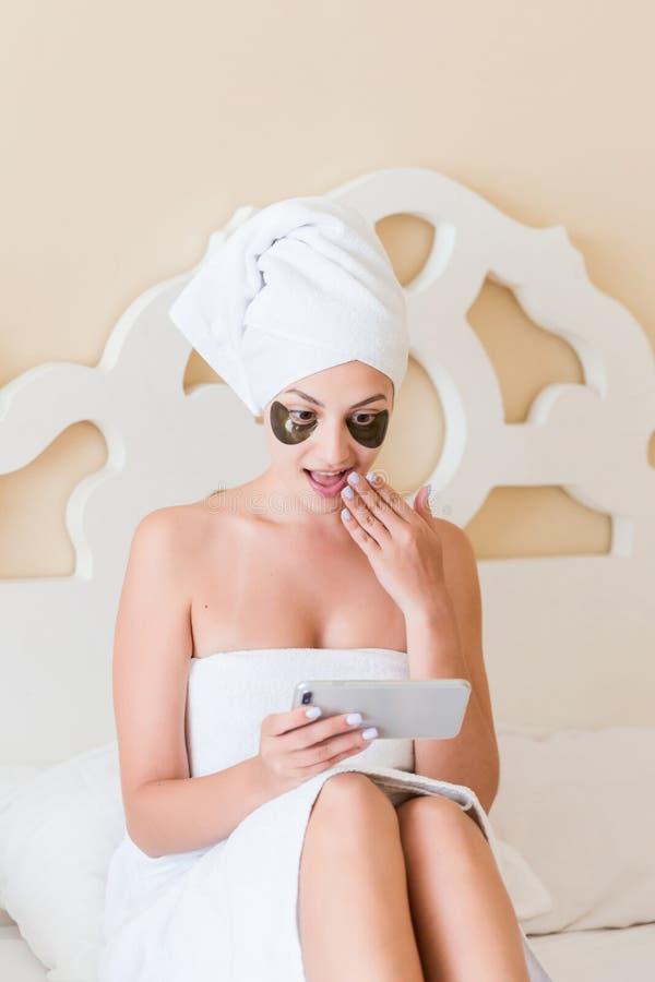 La jeune femme étonnée ou choquée avec les corrections de dessous d'oeil a obtenu une mauvaise nouvelle et téléphone portable d'u images stock