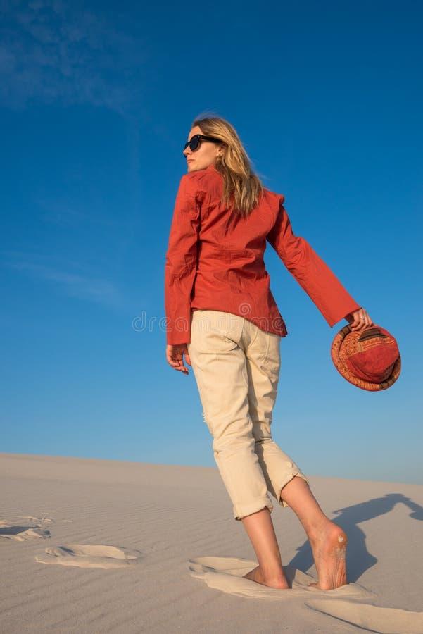 La jeune femme étonnante, blonde dans des lunettes de soleil marche par l'être photographie stock