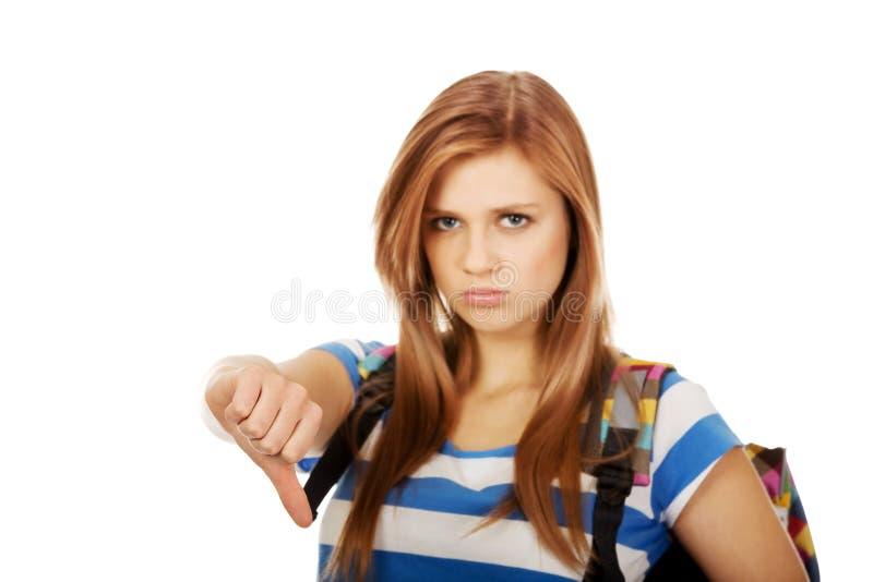 La jeune femme adolescente malheureuse montre des pouces vers le bas photographie stock libre de droits