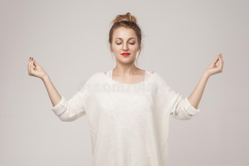La jeune femme adulte de Blone fermée, détendent et faisant l'asana de youga image libre de droits