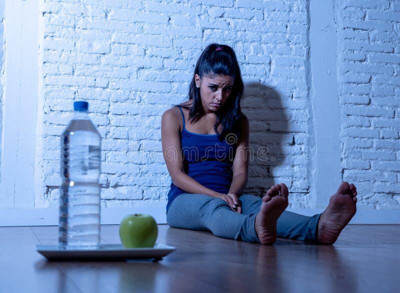 La jeune femme affamée déprimée sur la pomme et l'eau suivent un régime photo libre de droits