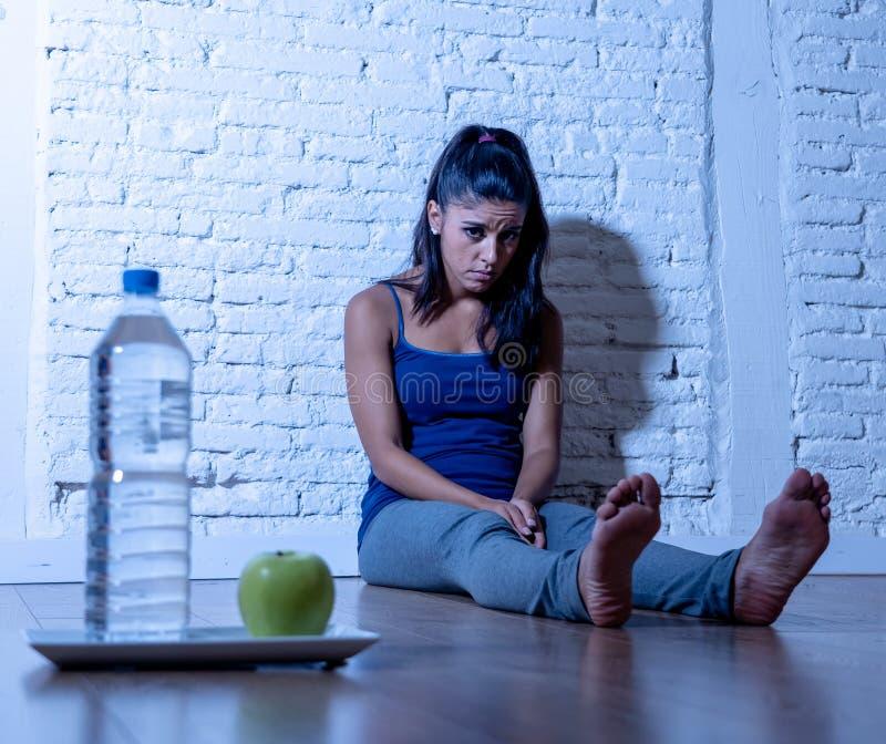 La jeune femme affamée déprimée sur la pomme et l'eau suivent un régime image stock