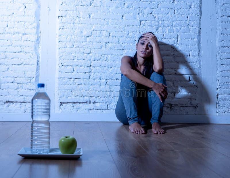 La jeune femme affamée déprimée sur la pomme et l'eau suivent un régime photographie stock