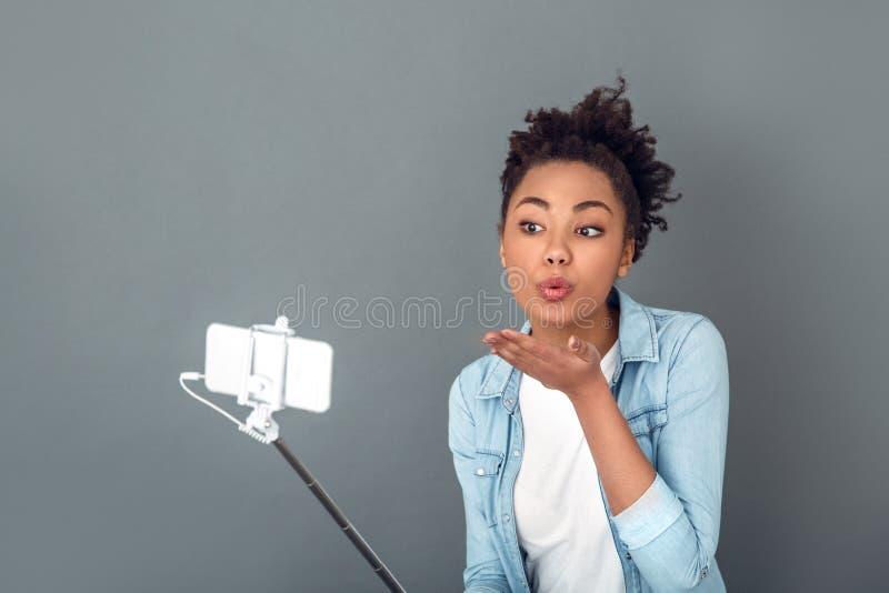 La jeune femme africaine d'isolement sur le mode de vie quotidien occasionnel de studio gris de mur s'embrassent images libres de droits