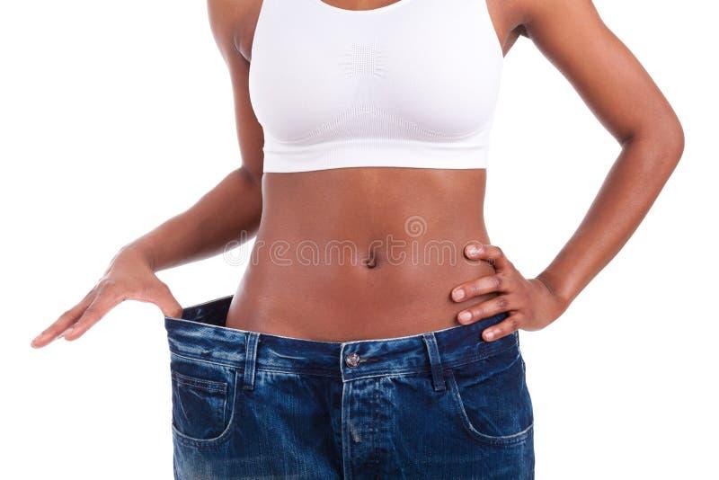 La jeune femme africaine dans de vieux jeans halètent après poids perdant images stock