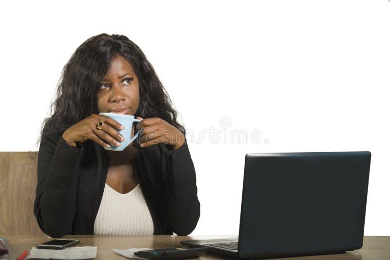 La jeune femme afro-américaine noire heureuse et attirante d'affaires travaillant à la tasse de boissons de bureau d'ordinateur d images stock