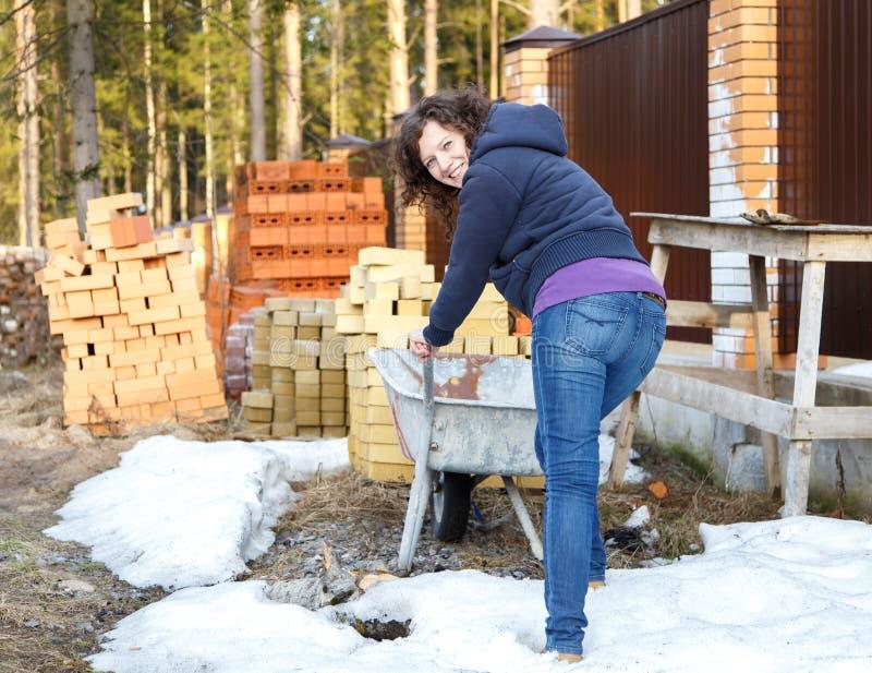 La jeune femme apprécie le travail en nature sur le chantier de construction photos stock