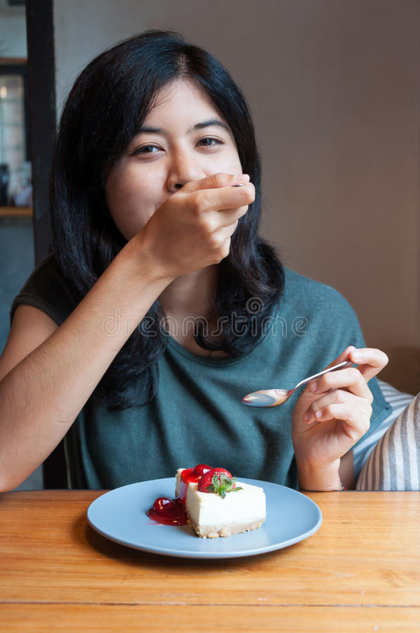 La jeune femme apprécient avec un gâteau en café photographie stock