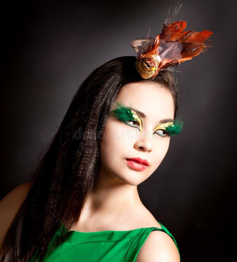 La jeune femme asiatique avec fasionable composent et modèle d'oiseau photos stock