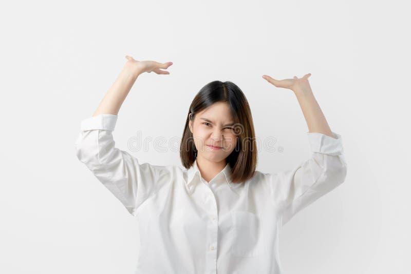 La jeune femme asiatique dans des vêtements sport blancs essayent de juger quelque chose lourde d'en haut photo libre de droits