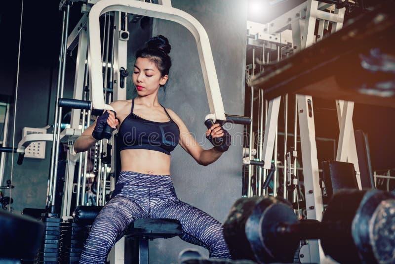 La jeune femme asiatique de forme physique exécutent l'exercice avec l'exercice-machine photos libres de droits