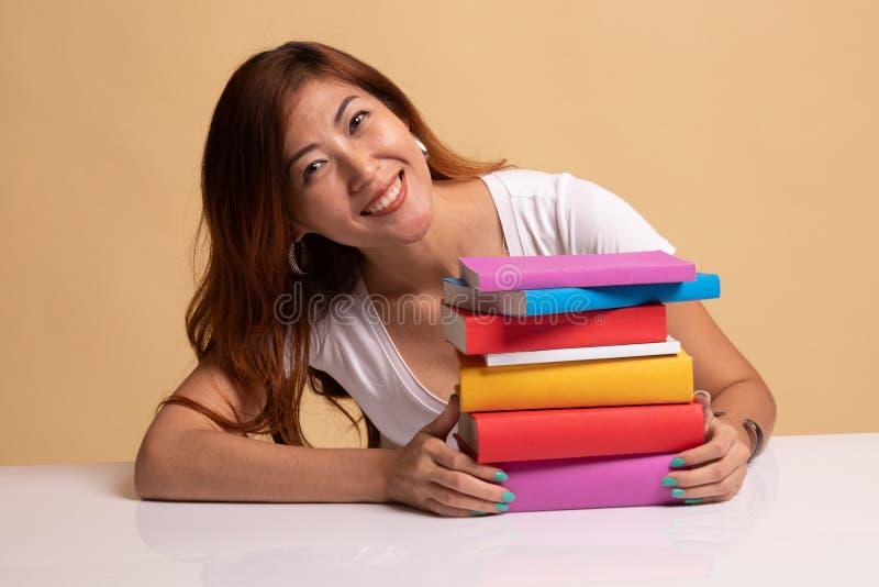 La jeune femme asiatique heureuse a lu un livre avec des livres sur la table photo libre de droits