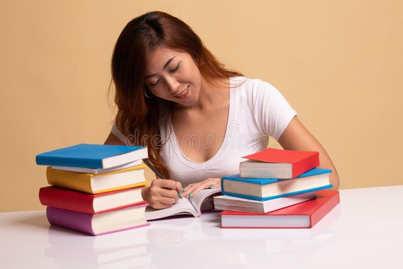 La jeune femme asiatique a lu un livre avec des livres sur la table photographie stock libre de droits