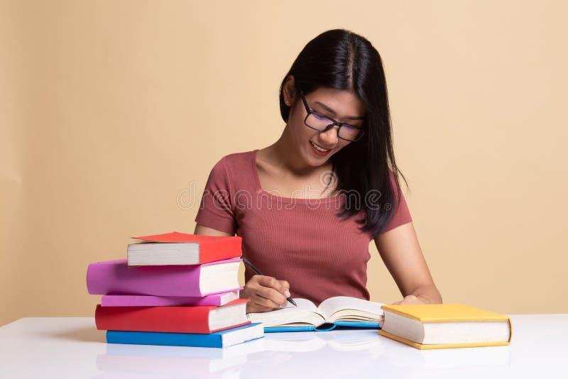 La jeune femme asiatique a lu un livre avec des livres sur la table images stock