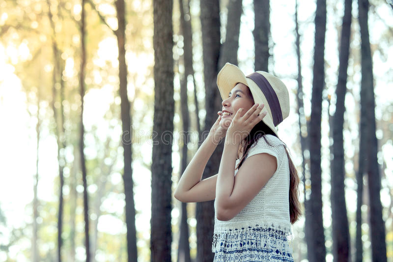 La jeune femme asiatique a mis dessus le chapeau et apprécier la nature images libres de droits