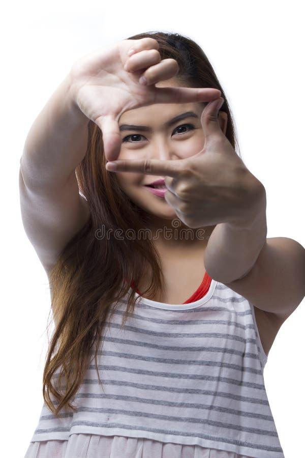La jeune femme asiatique montrant le doigt de vue se connectent le fond blanc images libres de droits